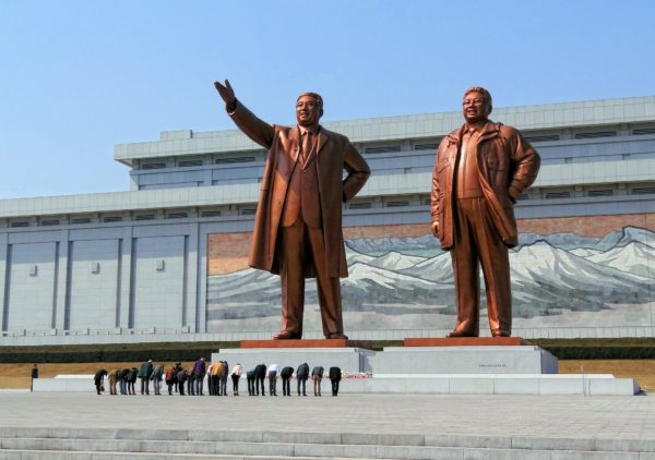 Group of people bowing in front of the statues of Kim Il-sung and Kim Jong-il at the Mansudae Grand Monument