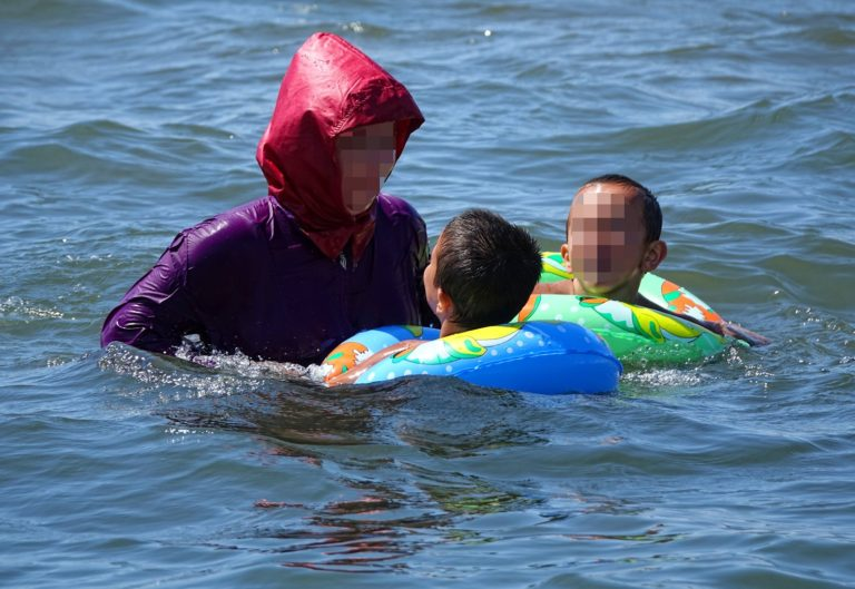 A mother playing with her children while wearing a burkini in the water.