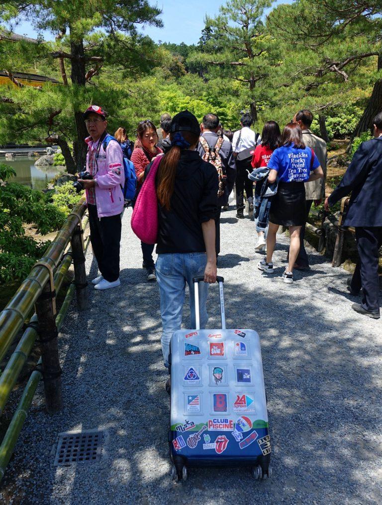 Tourist with hand luggage at Kinkaku-ji Golden Pagoda in Kyoto, Japan.