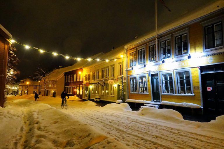 Bicyclist moving through snowy street in Bakklandet.