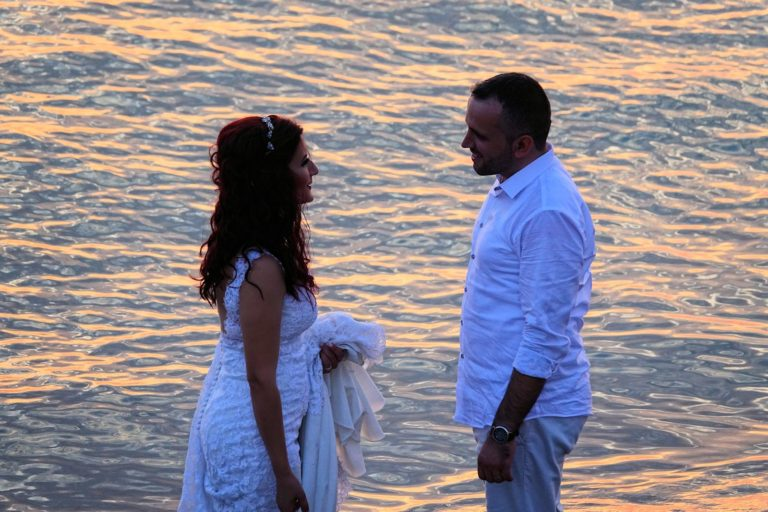 Newlyweds posing romantically on a beach in Durrës, Albania.