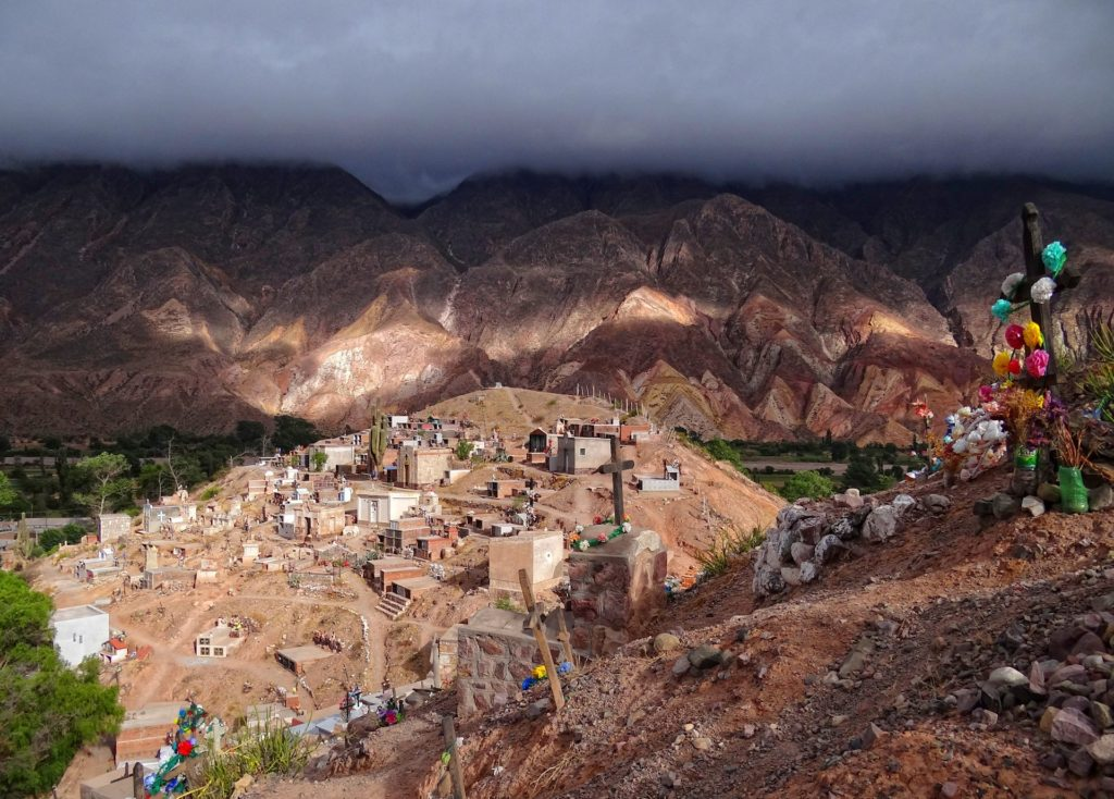Dramatic light on the cemetery of Maimares town opposite the colored mountains of Quebrada Humahuaca.