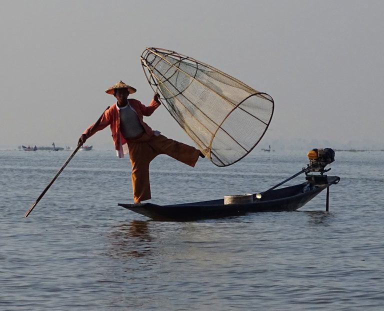 Photo of man posing for tourists on Inle Lake.