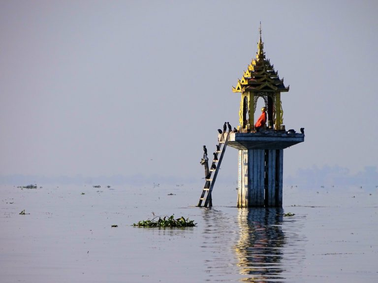 Photo of golden Buddha sitting in a shrine on Inle Lake.