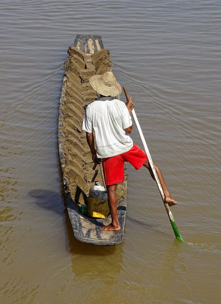 A man casually rowing his boat across Inle Lake, using one leg and an arm.