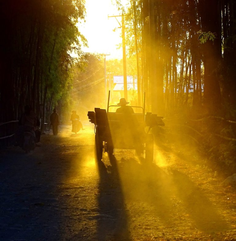 Rays of light becoming particularly visible in the road dust of dry Myanmar.