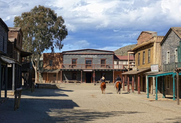 Cowboys riding through main street in Fort Bravo.