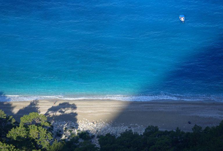 Photo of man walking on beach below Alinca, Turkey.