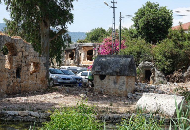 Photo of Lycian tombs at a parking lot in Ucagiz, Turkey.