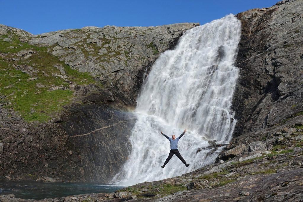 Bjørn Christian Tørrissen jumping in front of Grunnvassfossen in Lomsdal-Visten National Park, Norway.