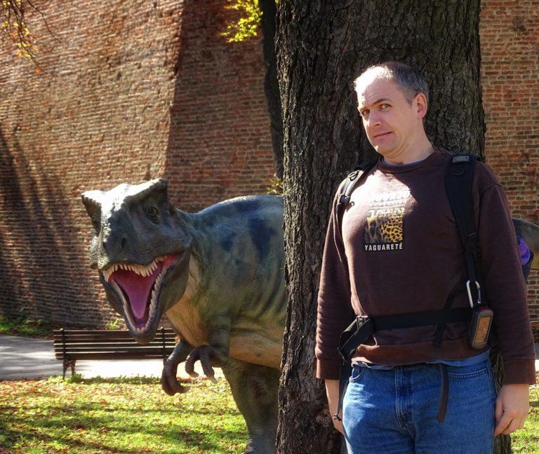Photo of man hiding from dinosaur in Belgrade, Serbia.