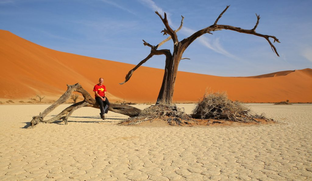 Photo of man sitting on a dead tree in Hiddenvlei, Namibia.