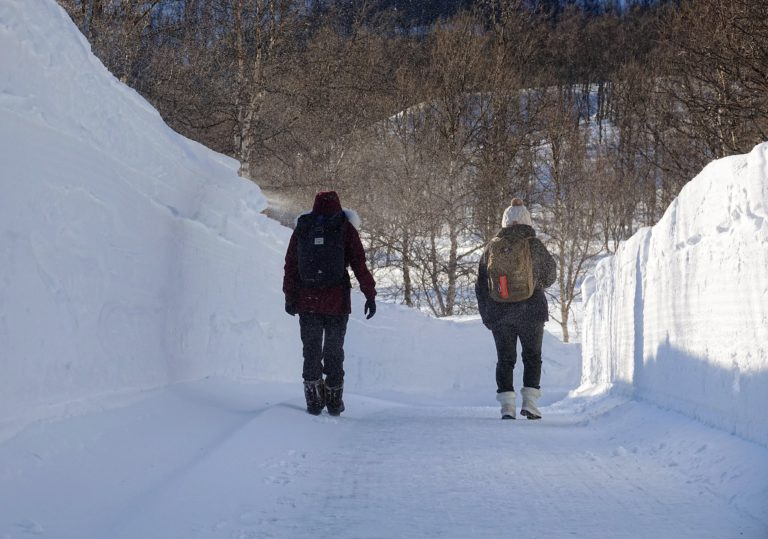 Photo of two people walking on a road surrounded by walls of snow
