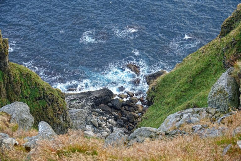 Photo of steep cliff from above, on Runde, Norway.