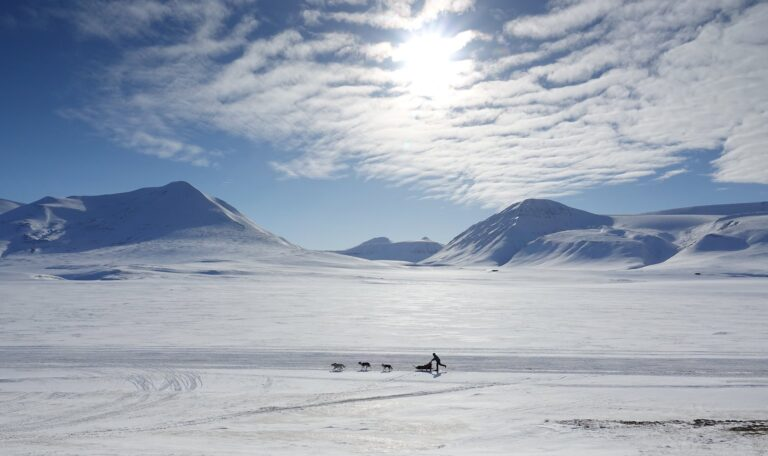 Photo of dogsledding in Adventdalen, Svalbard. In the background is Foxdalen.