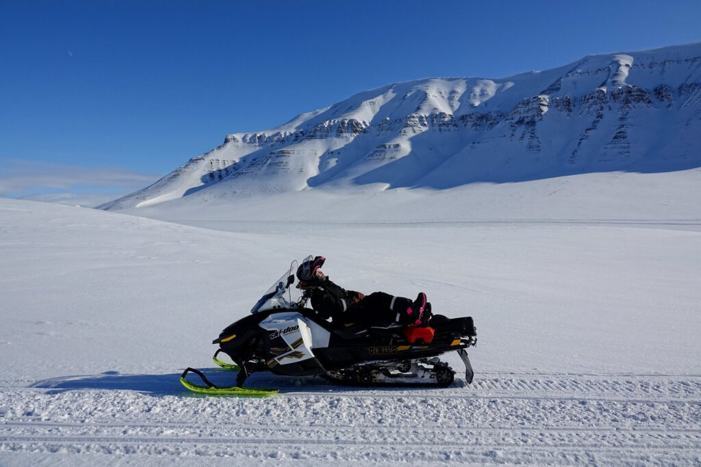 Photo of Arctic guide resting on a snowmobile in Eskerdalen, Svalbard.