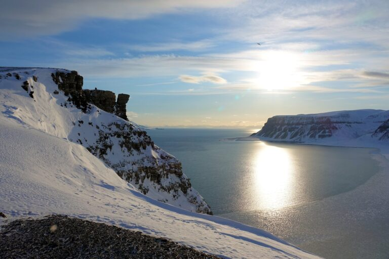 Photo of evening sun at the cliffs of Fjordnibba, with Tempelfjorden and Sassenfjorden in the background.