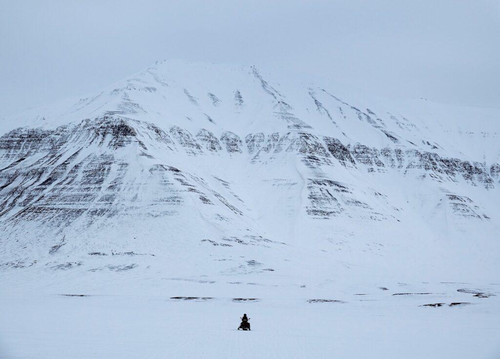Photo of snowmobile in front of Trehøgdene in Sassendalen, Svalbard, returning from Tempelfjorden and driving towards Longyearbyen.