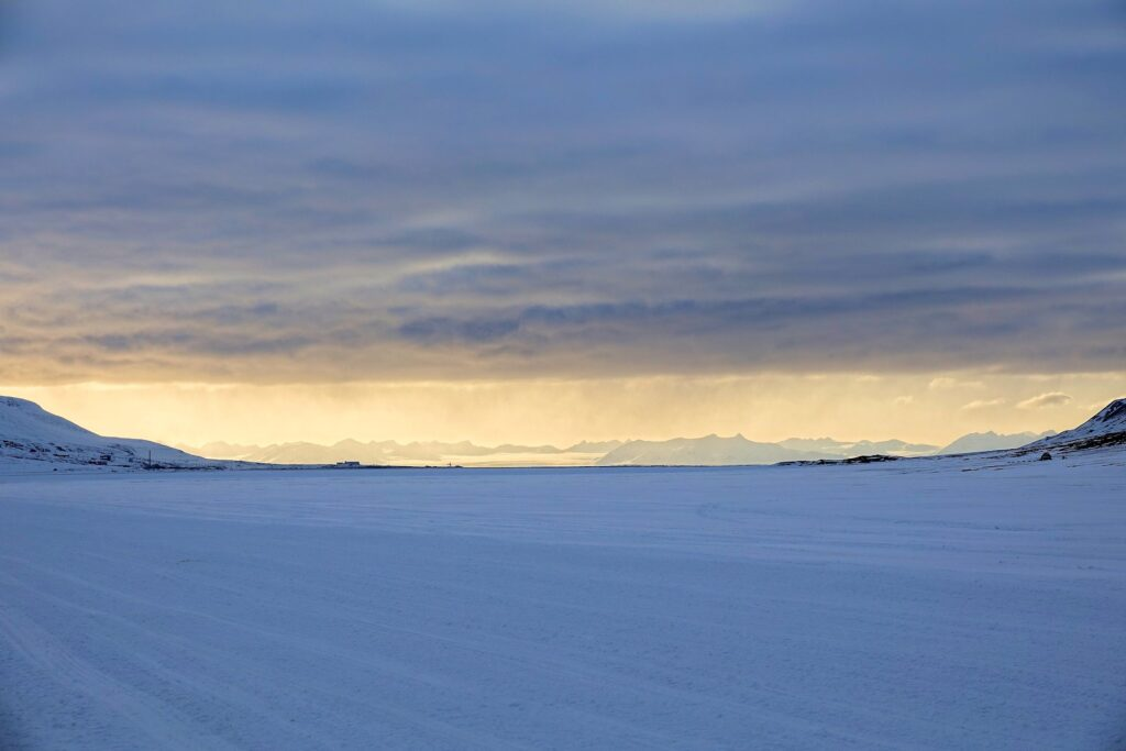 Photo of Longyearbyen and Oscar II Land silhouetted against an April sunset seen from Adventdalen.