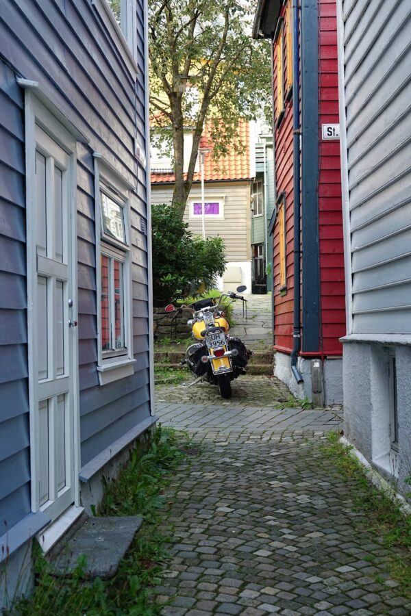 Photo of narrow streets in Bergen and a motorcycle.